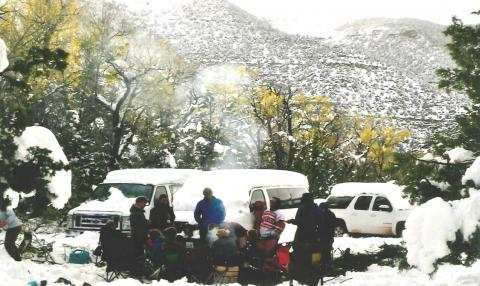 a group gathered around a campfire with snow coating the ground and vehicles parked behind them