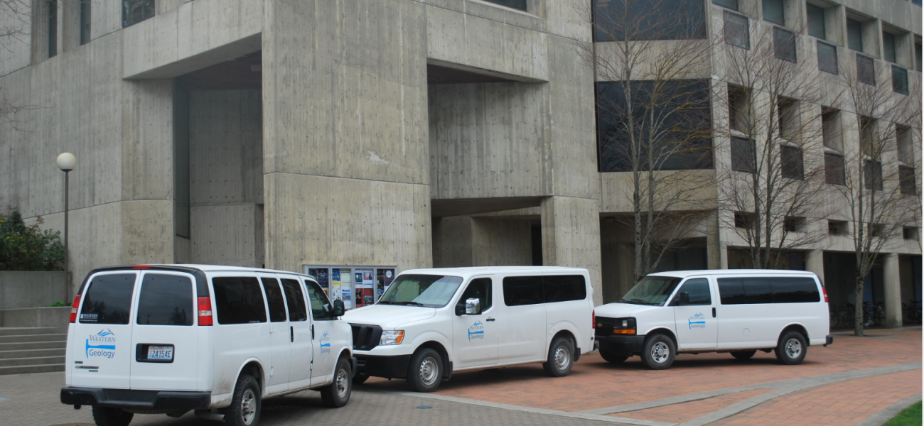 The lower level of the environmental sciences building with white vans parked out front